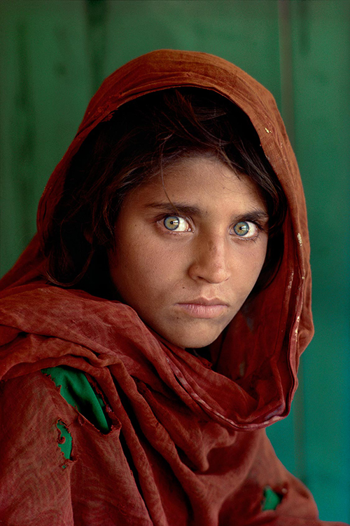 "Sharbat Gula, Afghan Girl, at Nasir Bagh refugee camp near Peshawar, Pakistan, 1984. National Geographic. ""The green-eyed Afghan girl became a symbol in the late twentieth century of strength in the face of hardship.  Her tattered robe and dirt-smudged face have summoned compassion from around the world;  and her beauty has been unforgettable.  The clear, strong green of her eyes encouraged a bridge between her world and the West.  And likely more than any other image, hers has served as an international emblem for the difficult era and a troubled nation."" - Phaidon 55 NYC5958, MCS1985002 K035 Afghan Girl: Found National Geographic, April 2002"